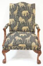 WIDE CARVED ARM CHAIR W/ HAIRY PAW FEET FRONT AND BACK. UPHOLSTERY HAS JUNGLE ANIMALS. 30 1/2 IN WIDE, 43 1/2 IN H