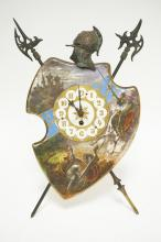 FRENCH HAND PAINTED PORCELAIN SHIELD FORM CLOCK WITH AN EASEL STYLE STAND SURMOUNTED BY A HELMET AND 2 EDGED WEAPONS. BACK MARKED *BREVETE S.G.D.G. , L.E.B*. HAS SOME WEAR TO THE PAINT. 16 1/4 INCHES TALL. 11 1/2 INCHES WIDE.