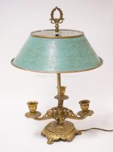 BRONZE TABLE LAMP WITH ELECTRIC FIXTURE IN THE CENTER SURROUNDED BY 3 CANDLE CUPS. PAINTED SHADE HAS WEAR. 18 3/4 INCHES TALL.