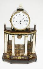 FRENCH CLOCK WITH BRONZE MOUNTS, 4 COLUMNS ACROSS THE FRONT WITH A MIRRORED BACK SURROUNDING A PAINTED FLOOR. FACE READING *FRANZ KAPRALECH* AT THE TOP AND *IN MARIA ENZERSTORF* AT THE BOTTOM. 20 3/4 INCHES TALL. MISSING 2 BRONZE STRIPS ON THE REAR FINIALS. SOME CHIPPING TO THE PORCELAIN FACE, SOME VENEER LIFTING, AND A CRACK IN EACH OF THE SIDE COLUMNS.