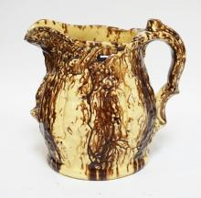 OVERSIZED BENNINGTON POTTERY PITCHER WITH HANGING GAME ANIMALS INCL DEER, BOAR, ETC. HAS SOME GLAZE LOSSES & SOME CHIPS ON THE RIM. 9 1/2 INCHES TALL.