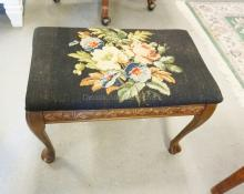 CARVED FOOTSTOOL WITH NEEDLEPOINT TOP. 20 1/2 X 12 3/4 INCH TOP. 14 1/2 INCHES TALL.