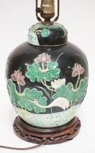 ORIENTAL JAR DECORATED WITH HERON & FLOWERS. LAMPED AND MOUNTED ON A CARVED WOODEN BASE. 25 1/4 INCHES TALL.