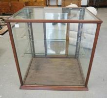 WOODEN DISPLAY CASE WITH ONE GLASS SHELF. 30 1/4 INCHES TALL. 29 1/2 INCHES WIDE.