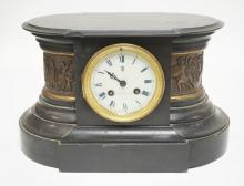 SLATE MANTEL CLOCK WITH A PORCELAIN FACE AND SCULPTED METAL BANDS ON THE SIDES OF MEN WITH CHARIOTS AND AN ELEPHANT. 13 1/2 INCHES WIDE. 8 1/2 INCHES TALL. TOP LEFT CORNER CHIPPED PLUS SOME OTHER SMALLER NICKS.