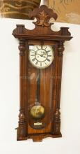 WALNUT REGULATOR CLOCK WITH A PORCELAIN FACE. 45 X 16 1/2 INCHES MISSING FINIALS.