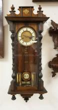 WALNUT REGULATOR CLOCK WITH A PORCELAIN DIAL. 32 X 12 1/4 INCHES.