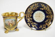 ROYAL VIENNA CUP & MATCHING SAUCER WITH A SCENE TITLED *AMOR ENTWAFFNET*. CUP IS SIGNED KAUFFMANN AND MEASURES 3 1/2 INCHES TALL. 5 1/4 INCH DIA.