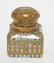 BRONZE MOUNTED CRYSTAL INKWELL. WREATH AND RIBBON DECORATION ON THE LID, LEAFY SWAG & COLUMN DECORATED BASE. 3 INCHES TALL. 2 1/4 INCHES SQUARE. SLIGHT ROUGHNESS ON CORNERS.