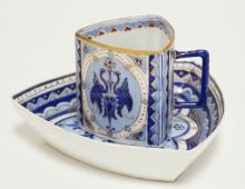 PIRKENHAMMER TRIANGULAR CUP & SAUCER. DECORATED IN BLUES WITH PHOENIX TYPE BIRDS ON THE SIDES OF THE CUP.