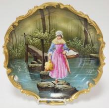 BLAKEMAN AND HENDERSON LIMOGES WALL PLATE W/ A WOMAN CROSSING A STREAM HOLDING A CHICKEN, A BASKET AND AN UMBRELLA. 12 1/4 IN. ARTIST SIGNED BAUMY.