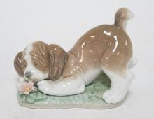 LLADRO *A SWEET SMELL* DOG WITH A FLOWER FIGURE. 4 INCHES HIGH.