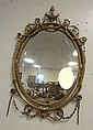 OVAL CUT MIRROR IN AN ORNATE MIRROR FRAMED