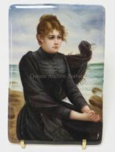 PAINTING ON PORCELAIN OF A LADY IN A BLACK DRESS SEATED AT THE SEASHORE. 3 1/2 IN X 5 IN