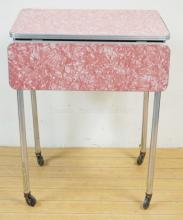 SMALL CHROME AND PINK FORMICA ROLLING DROP LEAF TABLE. 18 IN X 24 IN, DROPS ARE 7 1/2 IN, 29 3/4 IN H