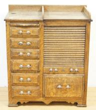 OAK DENTAL CABINET WITH 7 DRAWERS AND A ROLL UP DOOR WITH SWING OUT TRAYS. 29 IN WIDE, 31 IN TALL.