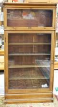 OAK GLASS DOOR BOOKCASE WITH STACKING TOP. 67 1/2 IN TALL & 34 IN WIDE.