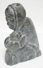 ESKIMO STONE CARVING OF A WOMAN HOLDING A BABY SEAL. 11 IN TALL.
