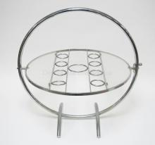 MID CENTURY MODERN CHROME COCKTAIL TABLE. FOLDS FLAT. HAS GLASS SIDE SURFACES AND RINGS TO HOLD A COCKTAIL SHAKER AND 8 GLASSES. SURFACE IS 20 7/8 IN DIA, 24 3/4 IN H