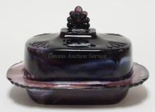 PURPLE SLAG COVERED BUTTER DISH. 8 1/8 X 6 1/4 AND 5 1/4 IN TALL. FLAT FLAKE ON CORNER.