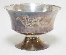 .835 SILVER (17.8 TROY OZ) HAND HAMMERED BOWL WITH A PEDESTAL FOOT AND FEMALE NUDE FIGURE ON THE SIDE. 8 5/8 IN WIDE, 6 IN TALL.