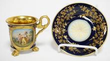 ROYAL VIENNA HAND DECORATED PORCELAIN CUP & SAUCER IN COBALT BLUE & GOLD WITH A VIGNETTE OF A WOMAN TAKING CUPIDS BOW. ARTIST SIGNED *KAUFFMANN*. TITLED ON THE BOTTOM *AMOR ENTWAFFNET* (LOVE DISARMED). CUP IS 3 1/2 INCHES HIGH AND THE SAUCER MEASURES 5 1/4 INCHES.