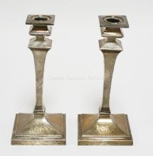 PAIR OF WEIGHTED STERLING SILVER CANDLESTICKS. EACH IS SLIGHTLY BENT. 8 5/8 INCHES TALL. EACH HAS A BASE PANEL ENGRAVED WITH SCROLLING INITIALS.