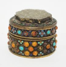 ENAMELED AND JEWELED ASIAN BOX WITH CARVED JADE INSET INTO LID. SOME JEWELS MISSING. 2 1/4 INCH DIA. 1 3/4 INCHES TALL.