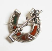 STERLING SILVER HORSEHOE & RIDING CROP PIN WITH INSET RED & GREEN STONE. 1 1/4 X 1 1/8 INCHES.