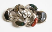 SILVER BROOCH WITH ENGRAVED DESIGNS ALONG WITH INSET STONES. 2 1/8 INCHES LONG.