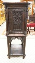 CARVED OAK CABINET WITH FULL FIGURAL CARVED COLUMNS WITH WITH IRON HARDWARE. 21 1/2 X 20 INCH TOP. 51 INCHES HIGH.