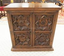 CARVED OAK 2 DOOR CABINET. STAR & FLOWER MEDALLION CARVINGS. 32 1/2 X 17 3/4 INCH TOP. 34 1/2 INCHES HIGH.