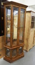 LIGHTED CURIO CABINET WITH GLASS SHELVES AND A MIRRORED BACK. 71 INCHES HIGH. 31 INCHES WIDE.