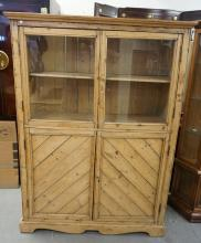 SCRUBBED PINE CABINET WITH 2 GLASS DOORS OVER 2 PANELED DOORS. 68 INCHES HIGH. 48 INCHES WIDE.