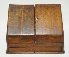 ANTIQUE OAK STATIONARY BOX WITH GLASS INKWELLS AND ORIGINAL RETAIL LABEL FOR THE CALENDAR REFILLS. 15 1/2 INCHES WIDE. 12 INCHES HIGH.