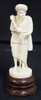 IVORY CARVING OF A MAN WITH A STAFF SMOKING A WATER PIPE. MOUNTED ON A WOODEN BASE. 7 3/4 IN H.