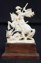 IVORY CARVING OF SAINT GEORGE SLAYING THE DRAGON. MOUNTED ON A WOODEN BASE. 5 1/2 IN H.
