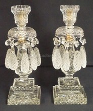 PAIR OF HEAVY CUT GLASS CANDLESTICKS W/ TEARDROP DIAMOND CUT PRISMS. ONE HAS A BROKEN SLEEVE BENEATH THE CANDLE CUP. 13 1/2 IN. H.