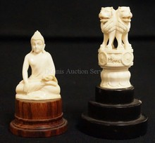 2 IVORY CARVINGS-BUDDHA AND 4 LIONS W/ MEDALLIONS OF OTHER ANIMALS AROUND THE CENTER BAND. BOTH MOUNTED ON WOODEN BASES. TALLEST 4 3/4 IN.
