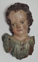 CARVED AND POLYCHROME DECORATED WOODEN HANGING BUST OF A CHILD. 9 IN H. HAS SOME CHIPS.