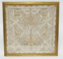 FRAMED EMBROIDERED TABLE COVER WITH SILVER THREADING. 21 INCHES SQUARE.