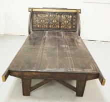 ASIAN OPIUM BED WITH PAINTED, BRASS STUDDED, AND CUTOUT METAL DECORATIONS. 48 INCHES WIDE. 80 INCHES LONG.