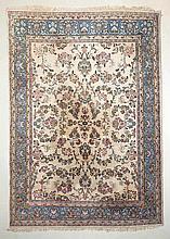 tapis iranien en laine à médaillon central rectangulaire à 3 médaillons de fleurs sur champ ivoire, bordure extérieure de fleurs sur champ ivoire.