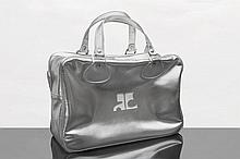 sac cabas Courrèges en cuir argenté, le devant est orné du sigle de la marque en blanc, fermeture éclair, double poignée, intérieur en blanc agrémenté d'une pochette zippée.