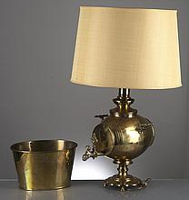 lampe à huile avec pied en laiton orné d'un tonnelet à deux anses sur piédouche, bec verseur avec embout sculpté en forme de jeune homme et de pomme de pin. On y joint un seau en laiton.