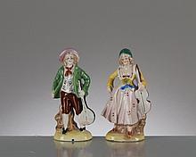 paire de figurines en faïence représentant une femme jouant du violoncelle et un homme jouant de la mandoline.