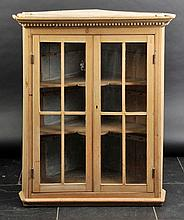 Cabinet. A Victorian pine hanging corner cabinet,  with dentil moulding, two gl