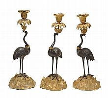 Three William IV gilt and patinated bronze candlesticks cast as standing storks