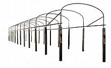 A wrought iron and oak mounted pathway bower frame