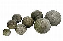 A set of eight graduated limestone spheres, 20th century